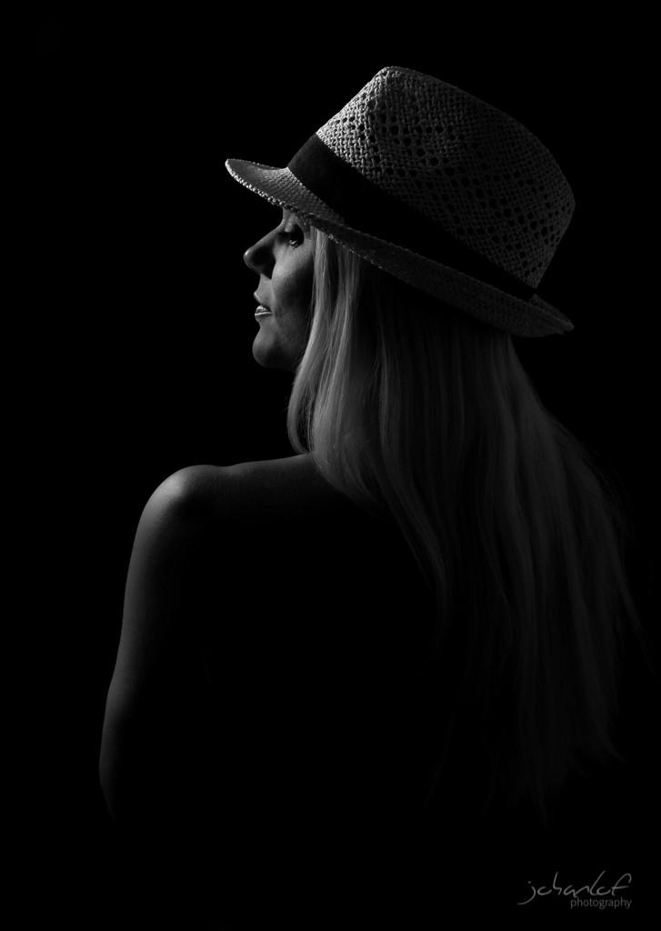 Svartvit silhuette av blond kvinna med stråhatt